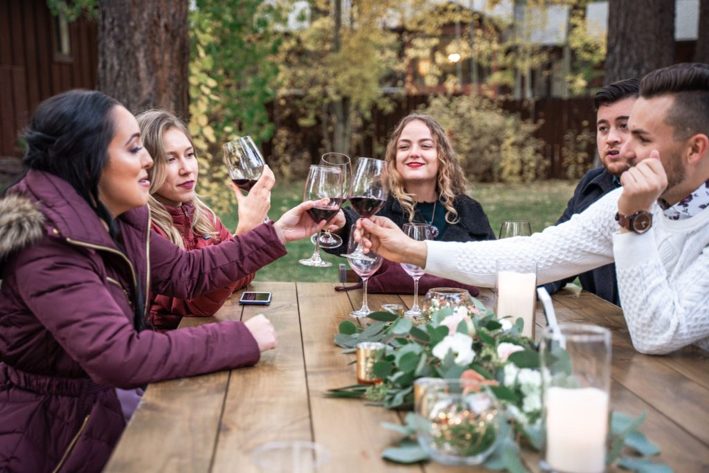 Wedding guests toast with red wine glasses
