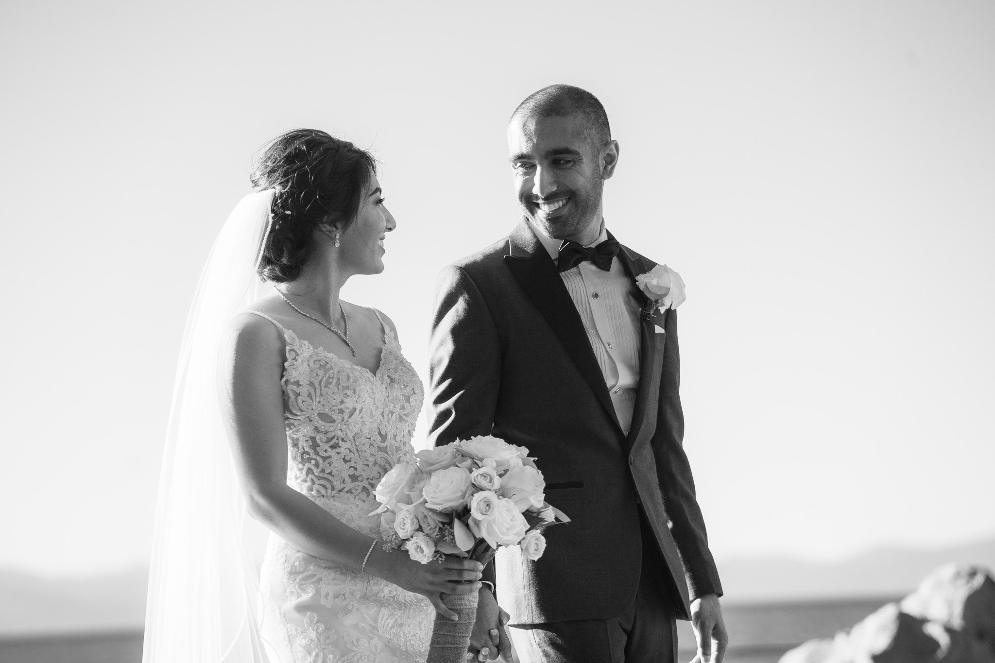 Groom smiles at the bride as they walk hand-in-hand after their marriage ceremony