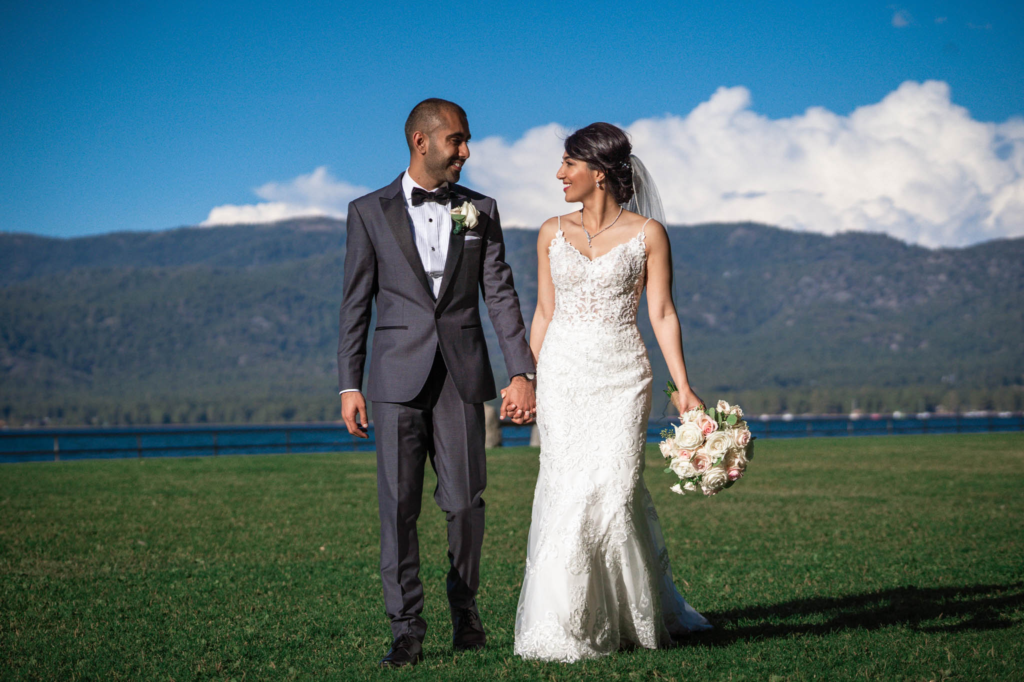 Bride and groom hold each other in front of a mountain backdrop in South Lake Tahoe
