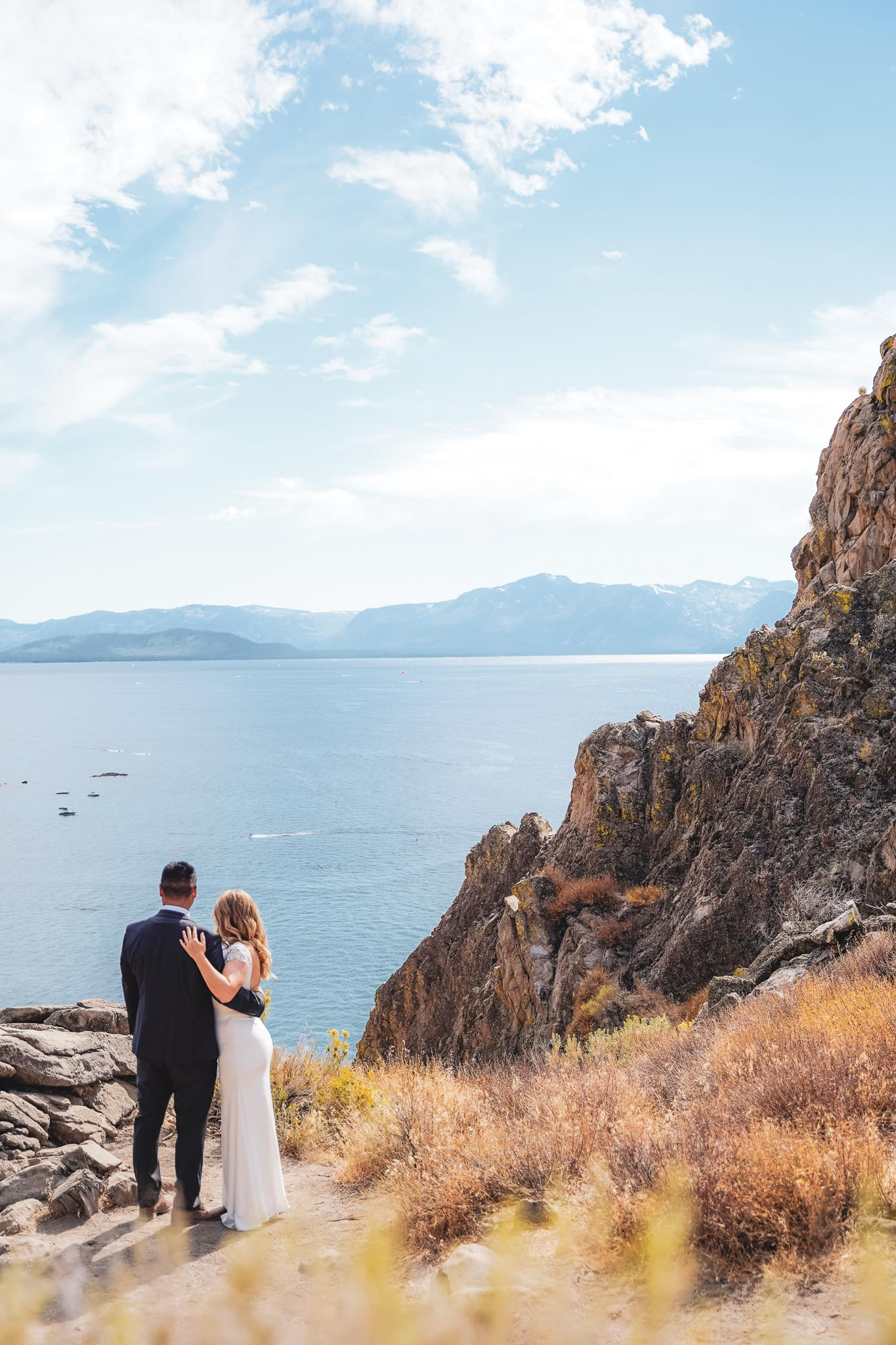 Bride and groom kissing with Lake Tahoe as a backdrop with mountains and lake