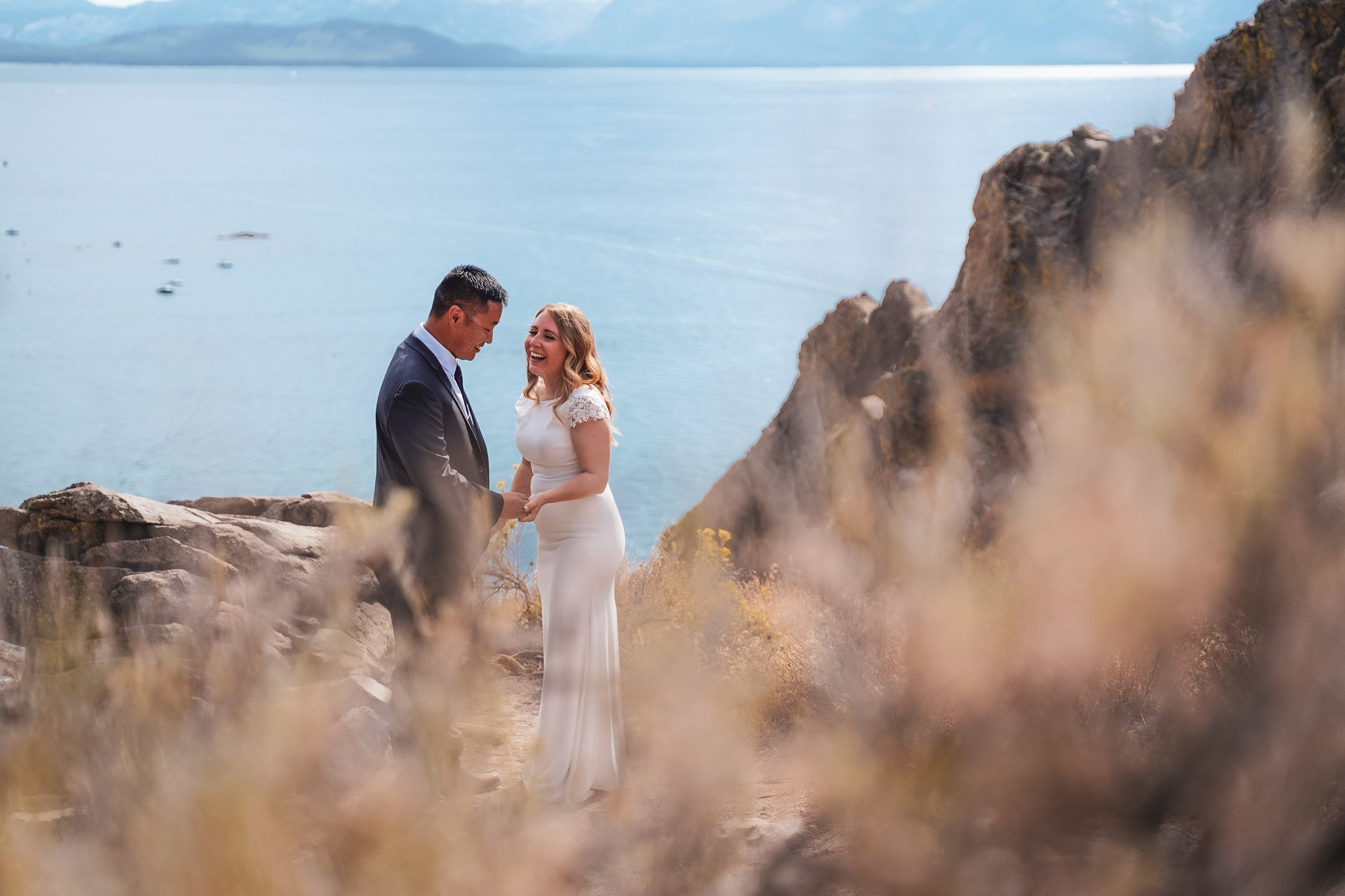 Bride and groom laughing with Lake Tahoe as a backdrop with mountains and lake