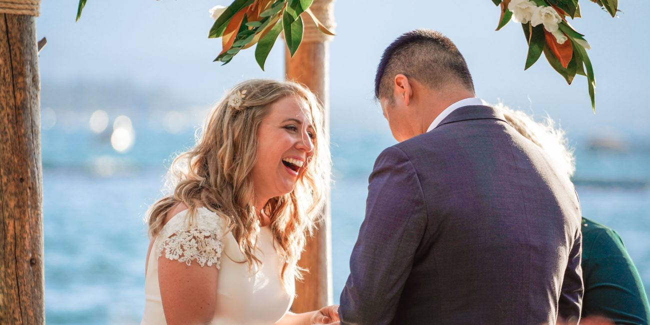 Bride laughing as they exchange rings at wedding at Lakeside Beach in South Lake Tahoe