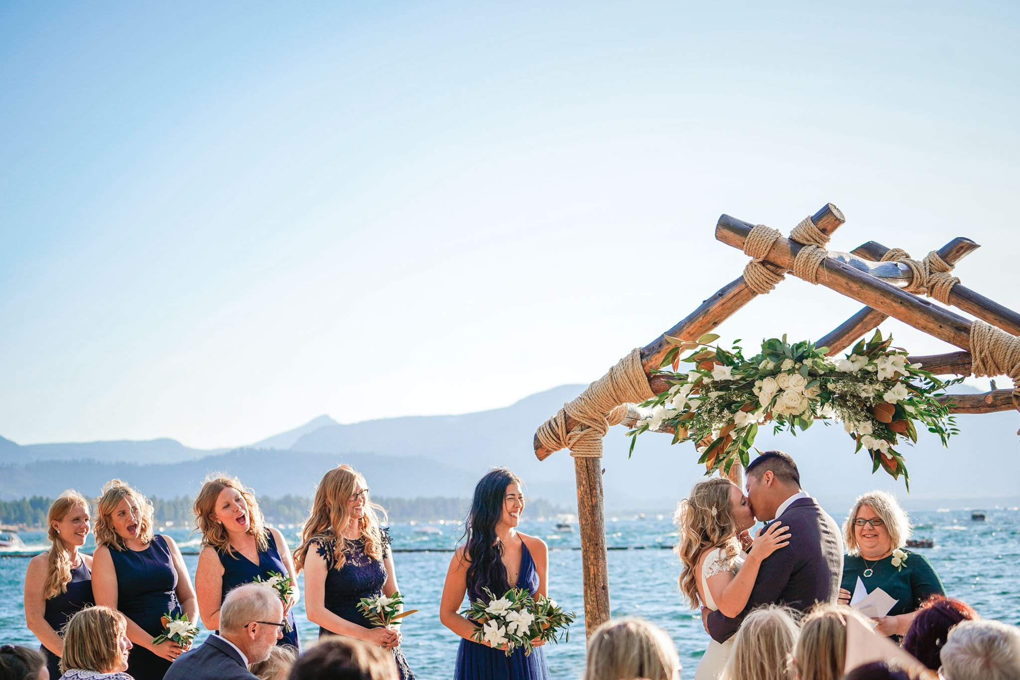 First kiss during a wedding ceremony with the bridesmaids smiling at Lakeside beach wedding