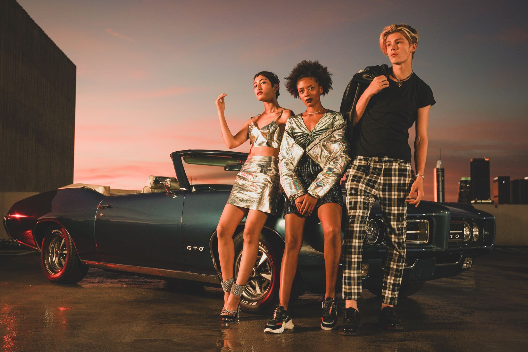 Three models in designer outfits standing in front of a classic car for a commercial photography shoot for special events