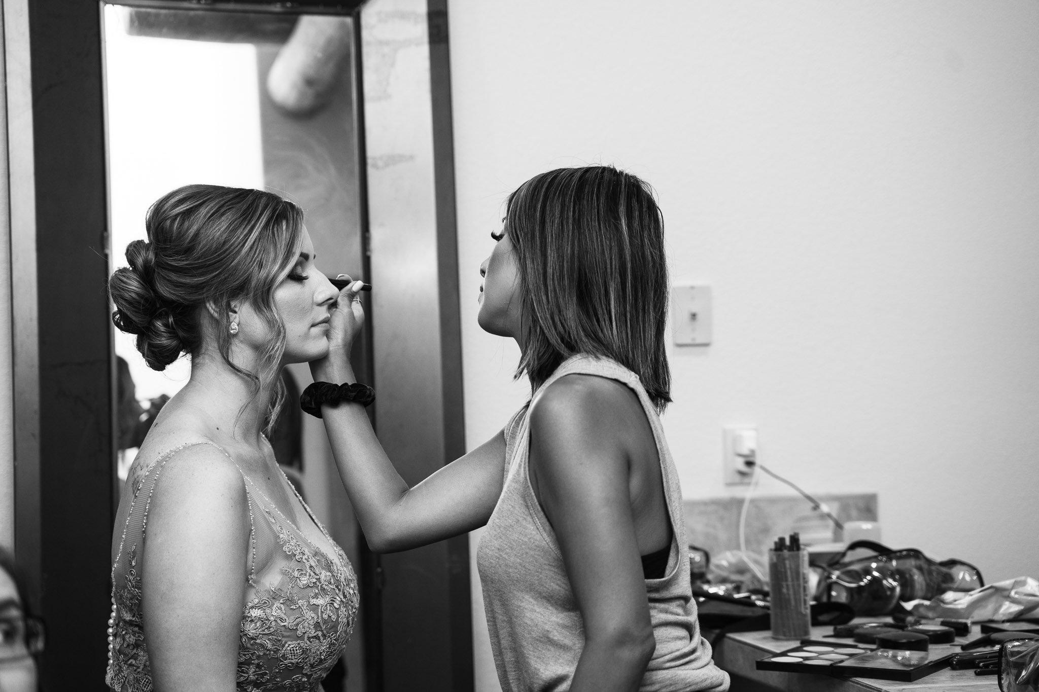 Makeup artist putting makeup on a bride