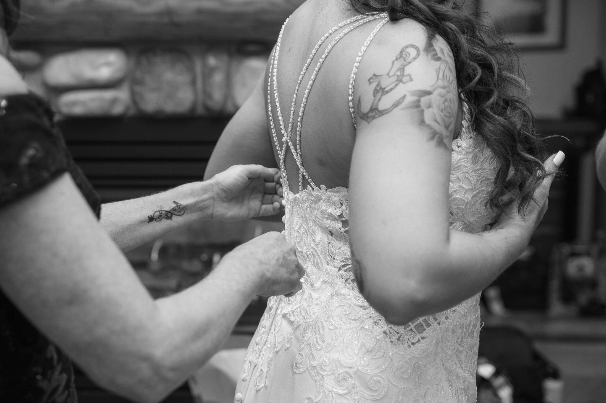 Mother helping bridge get into her wedding dres