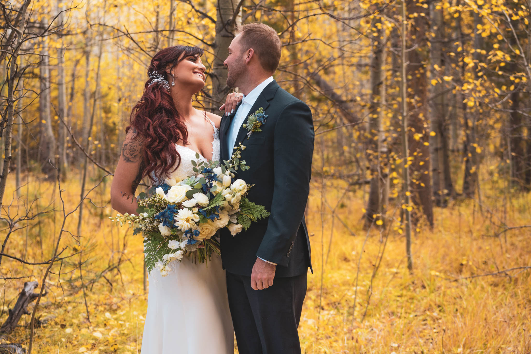 Bride and groom looking at each other surrounded by yellow aspen forest