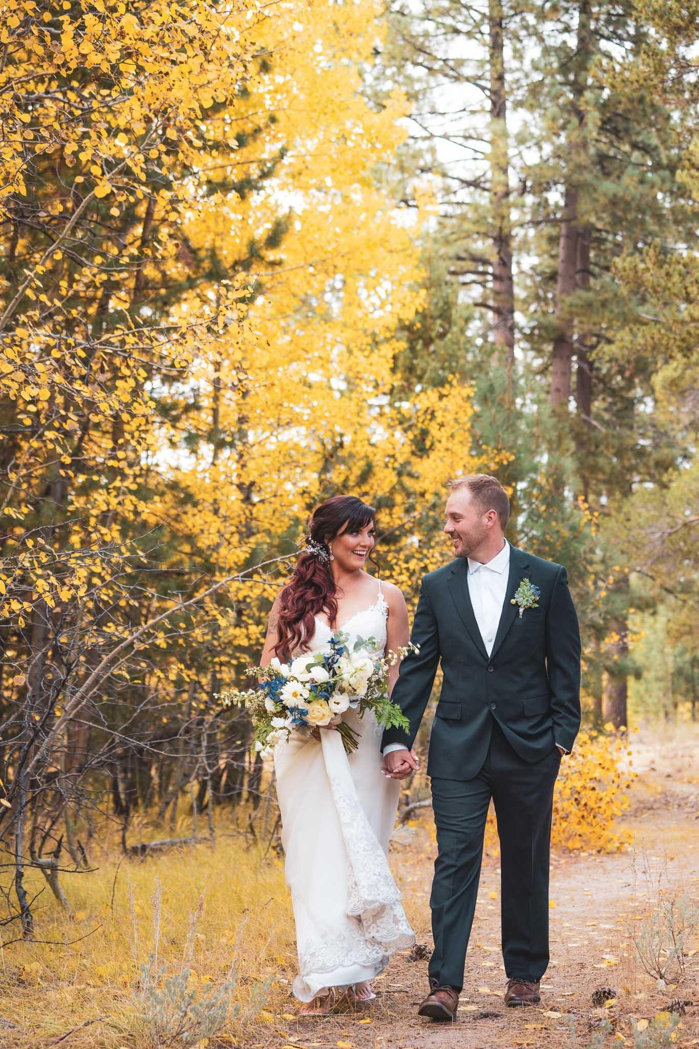 Bride and groom walking hand in hand between the aspens